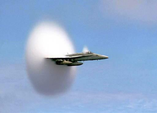 F18 Jet flys by a carrier and water precipitates from the shock wave in a donut-shaped cloud
